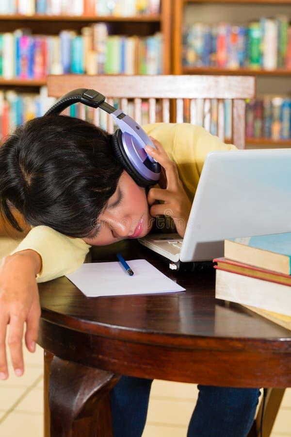 Moça na biblioteca com portátil e fones de ouvido imagem de stock