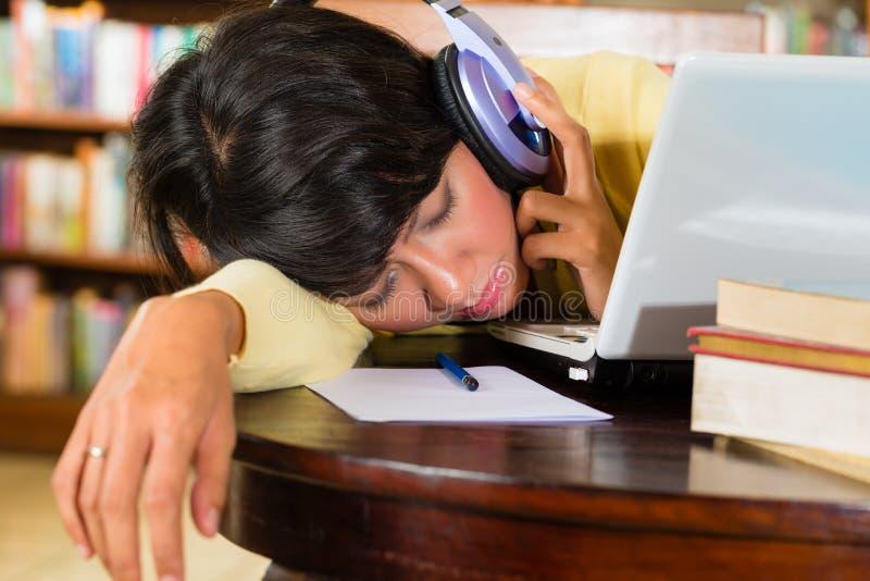 Moça na biblioteca com portátil e fones de ouvido foto de stock