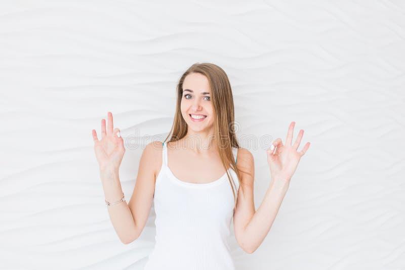 A moça na camiseta interioa branca que sorri com cara feliz mostra o sinal aprovado da mão foto de stock