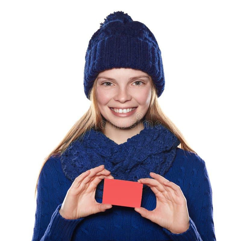 Moça na camiseta, no lenço e no chapéu da malha que guarda o cartão fotografia de stock royalty free