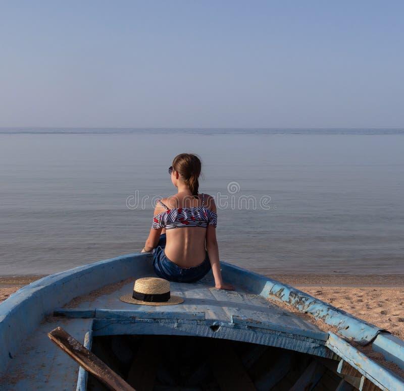 Moça na curva de um barco de madeira velho que olha o por do sol do mar imagem de stock