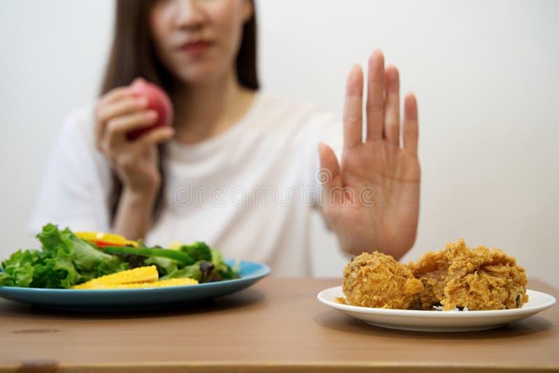 Moça na dieta para o conceito da boa saúde Feche acima da comida lixo de utilização fêmea da rejeição da mão eliminando seu favor foto de stock royalty free