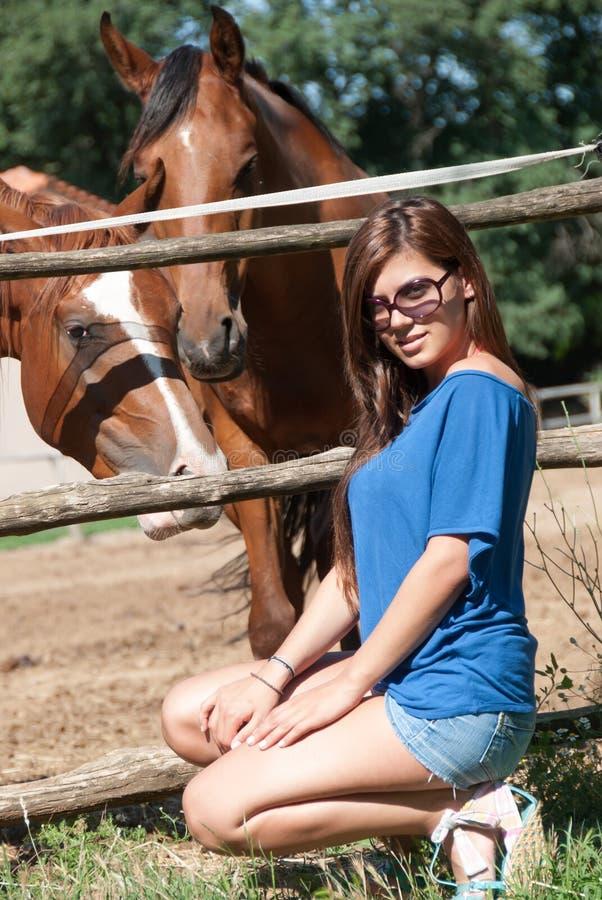 Moça na exploração agrícola cercada por cavalos fotografia de stock