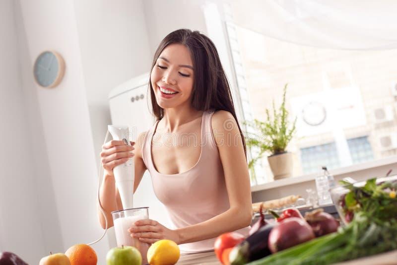 Moça na posição saudável do estilo de vida da cozinha que faz o iogurte de fruto com misturador da mão alegre imagem de stock royalty free