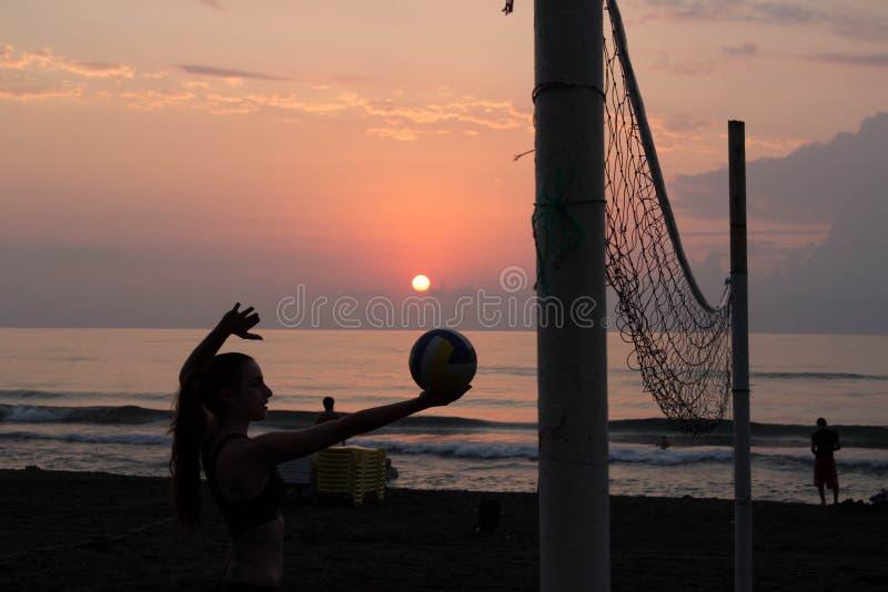 Moça na praia, guardando a bola nas mãos Redes do voleibol na praia imagem de stock royalty free
