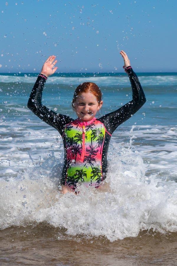 Moça na ressaca na praia de Makorori, perto de Gisborne, Nova Zelândia imagens de stock