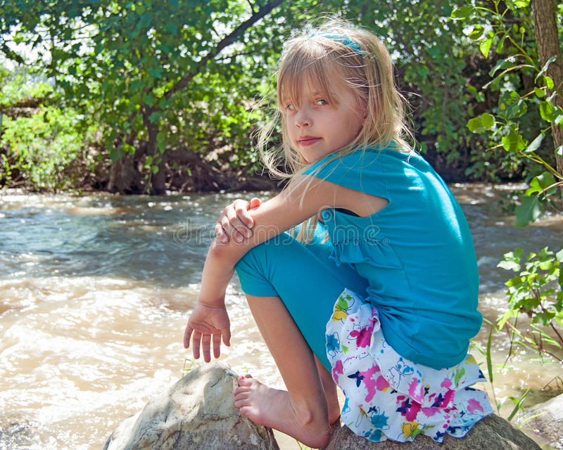 Moça na rocha pelo rio fotografia de stock royalty free