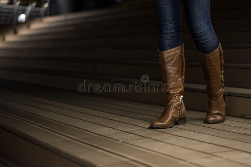 Moça nas botas de couro que anda abaixo das escadas imagem de stock