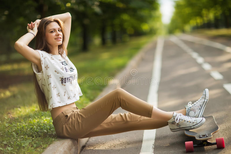 A moça nas sapatilhas e nas calças do t-shirt pôs sobre os pés e as mãos de um longboard atrás de seu retrato principal do estilo imagens de stock