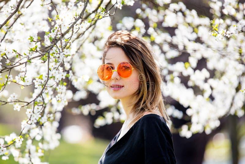 A moça no óculos de sol fica perto de uma árvore de florescência imagens de stock