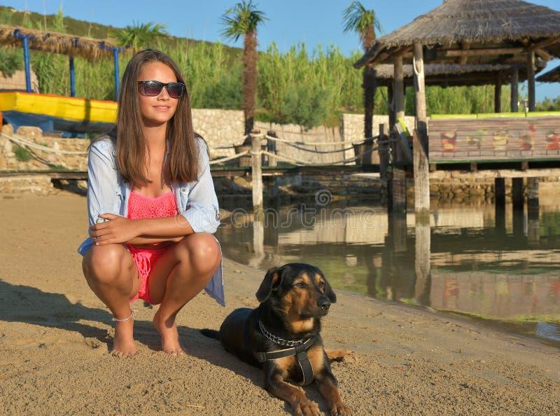 Moça no biquini e no cão na praia fotos de stock royalty free