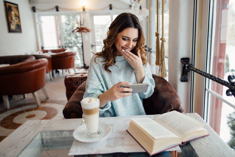 moça no café que olha o vídeo engraçado no telefone esperto e no riso imagem de stock royalty free
