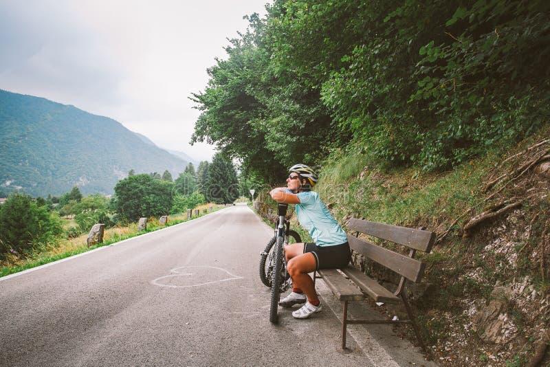 A moça no capacete e nos esportes veste sonhos de descanso de assento e vista para fora na distância em um banco de madeira em um foto de stock