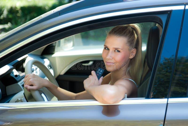 Moça no carro com chave do carro imagens de stock