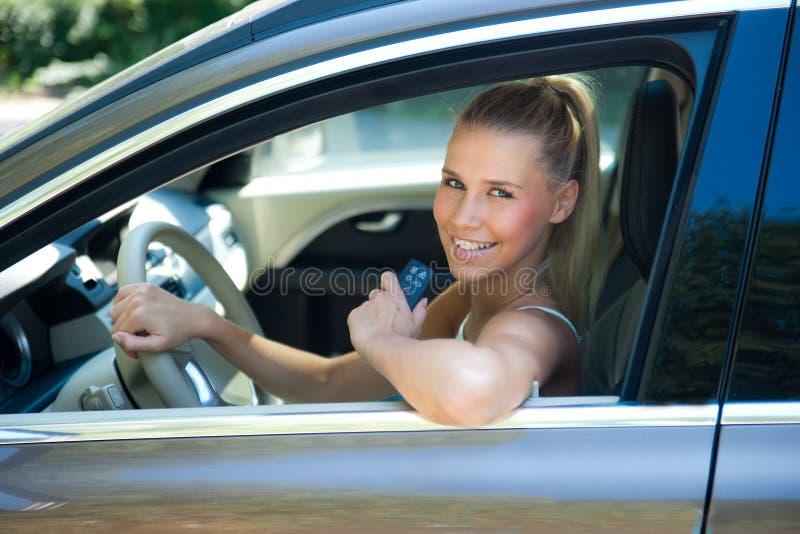 Moça no carro com chave do carro fotos de stock