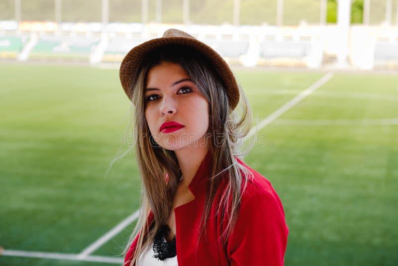 Moça no chapéu e terno vermelho no fundo de um campo de futebol fotos de stock