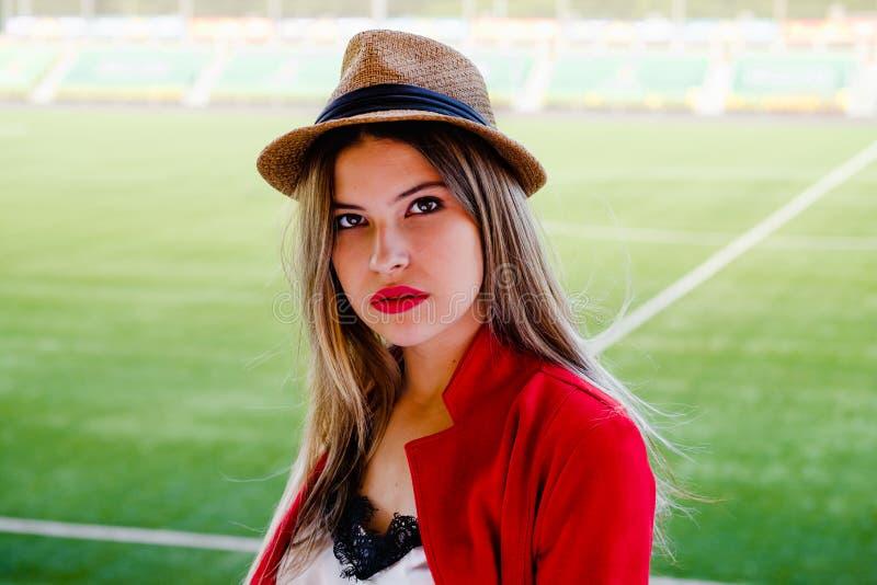 Moça no chapéu e terno vermelho no fundo de um campo de futebol imagem de stock royalty free