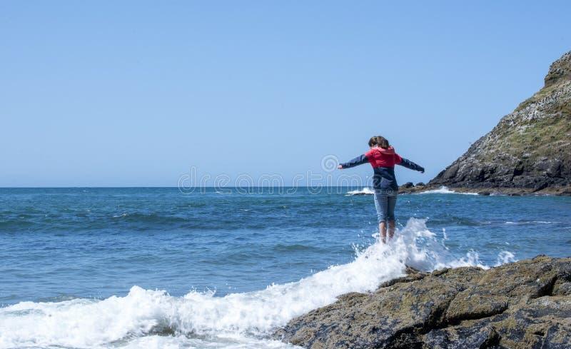 Moça no disjuntor de vento que está na rocha com as ondas que deixam de funcionar sobre seus pés foto de stock royalty free