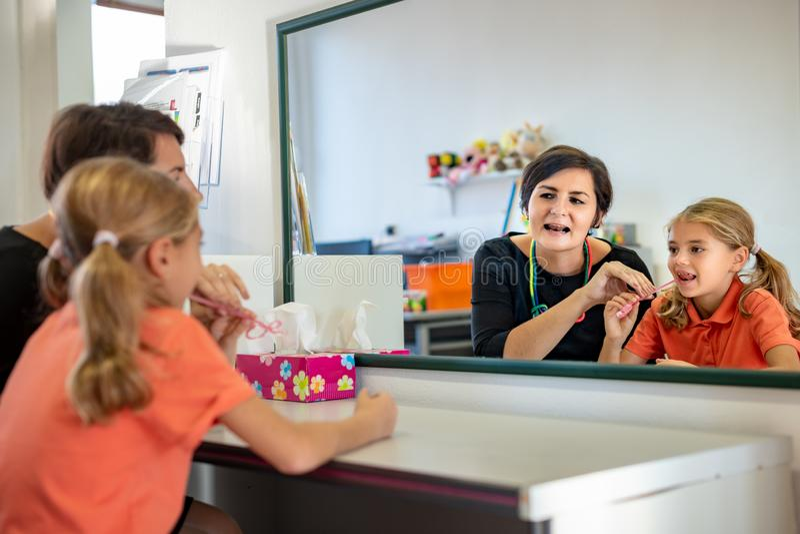 Moça no escritório da terapia da fala Reflexão de espelho da moça que exercita a pronunciação correta com terapeuta de discurso fotografia de stock royalty free