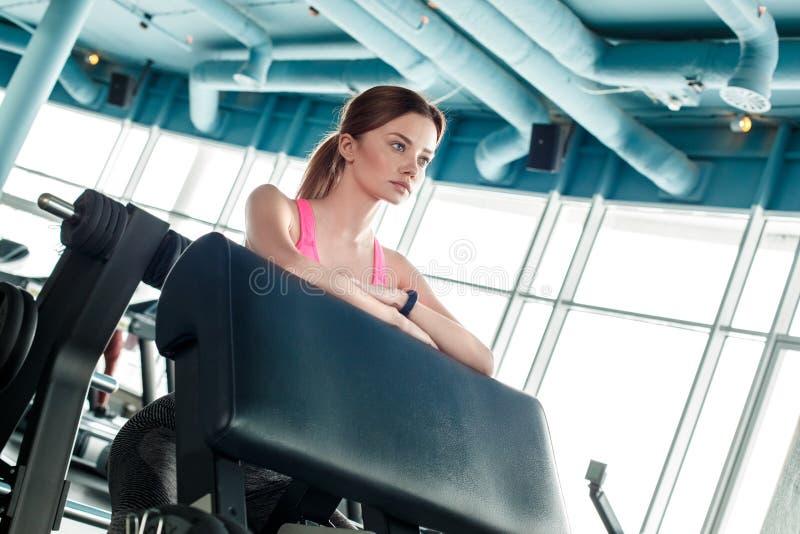 Moça no estilo de vida saudável do gym que inclina-se no instrutor motivado fotos de stock