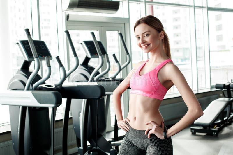 Moça no estilo de vida saudável do gym que levanta olhando a câmera alegre fotos de stock royalty free