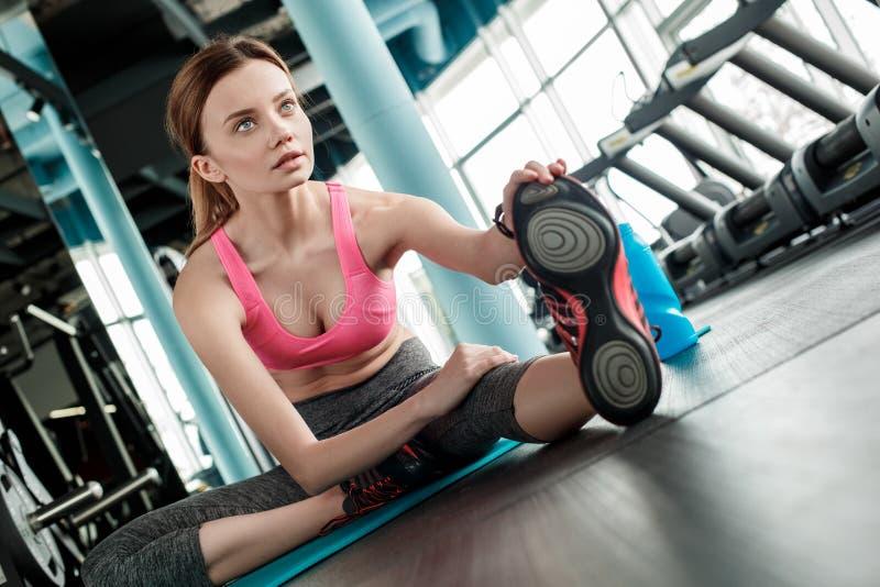 Moça no estilo de vida saudável do gym que senta-se na esteira que estica o pé que olha para a frente o close-up curioso fotografia de stock
