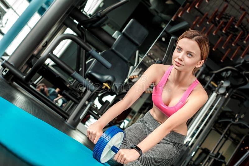 Moça no estilo de vida saudável do gym que senta-se na esteira que guarda a roda do ab que olha para a frente motivado fotografia de stock