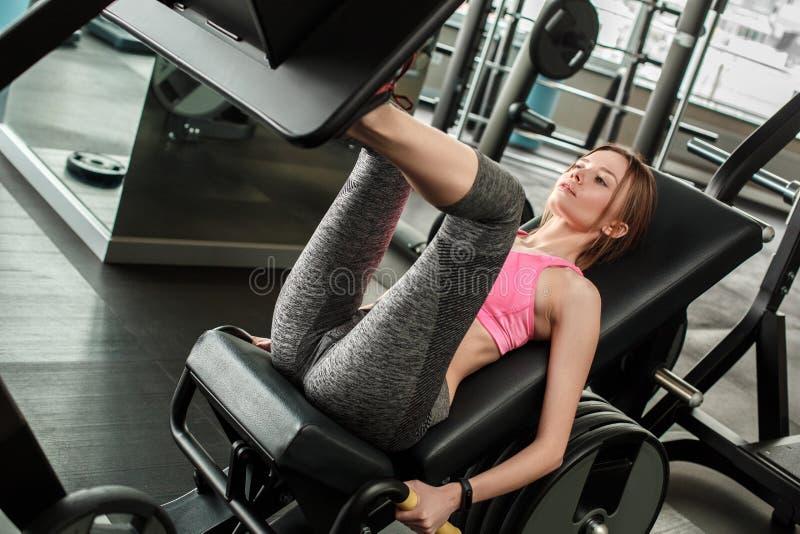 Moça no estilo de vida saudável do gym que senta-se na máquina que pressiona a placa concentrada fotos de stock royalty free