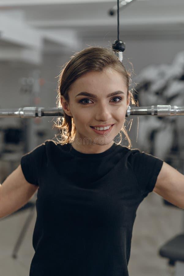 Moça no gym que executa exercícios imagem de stock