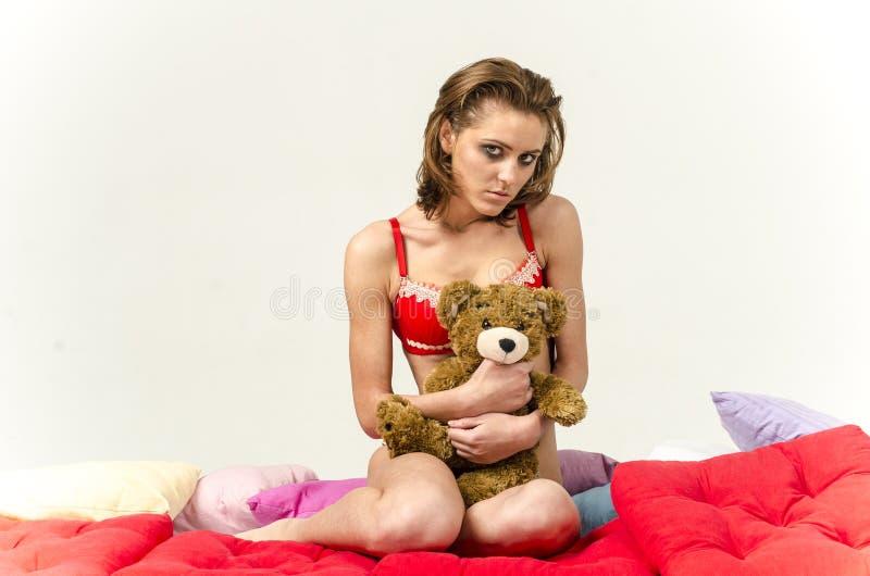A moça no roupa interior na cama que grita e que limpa rasga a mancha de suas mãos fotografia de stock