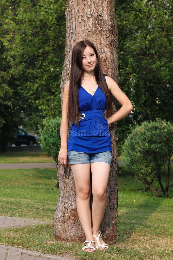 A moça no short inclinou-se contra uma árvore no parque imagem de stock