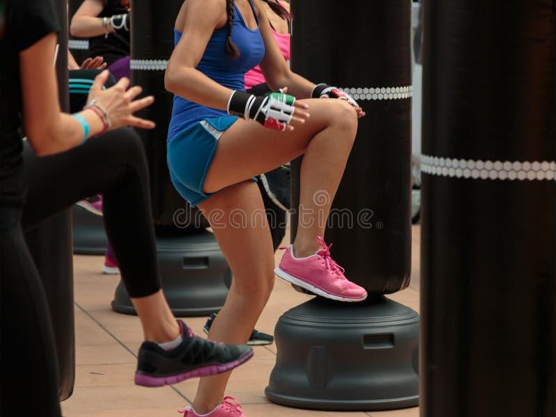 Moça no Sportswear azul: Exercício da aptidão e do encaixotamento com saco de perfuração imagem de stock royalty free