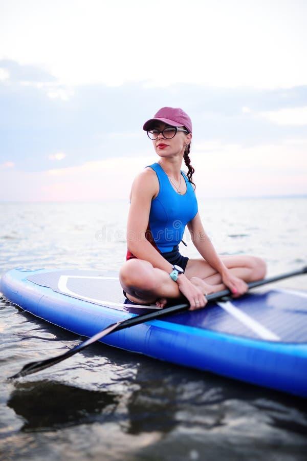 Moça no sportswear que senta-se em uma placa do SUP foto de stock royalty free
