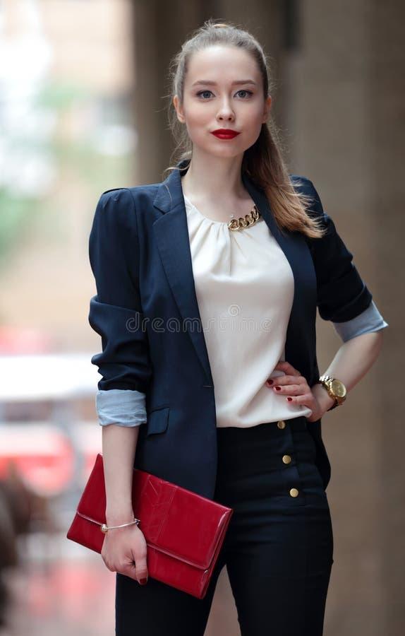 Moça no terno de negócio e em uma bolsa vermelha fotos de stock