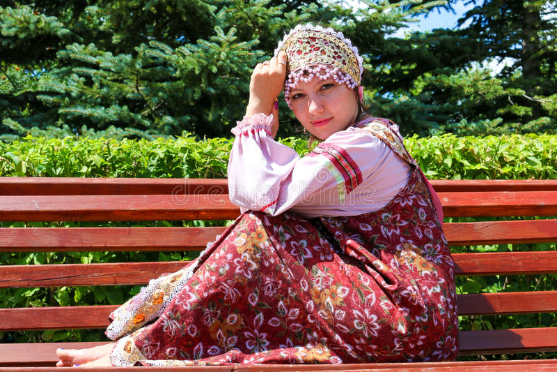 A moça no traje popular do russo senta-se no banco imagens de stock