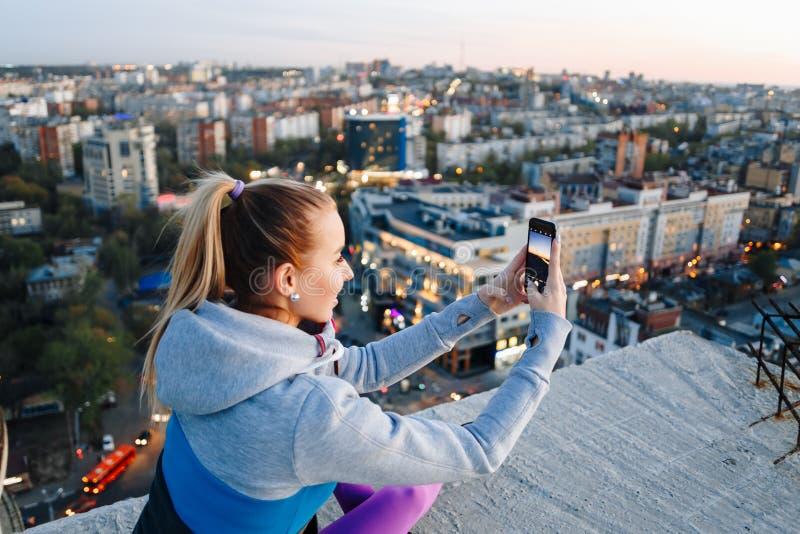 A moça no uniforme dos esportes toma fotos no telefone no telhado de uma construção sobre a cidade foto de stock