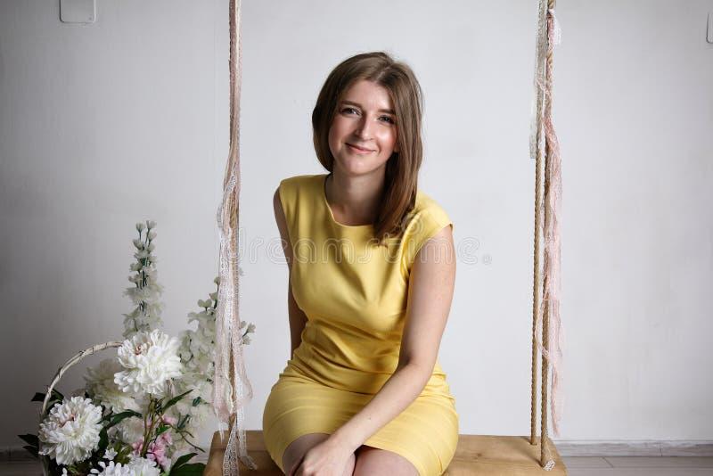 Moça no vestido amarelo no balanço na sala branca fotografia de stock royalty free