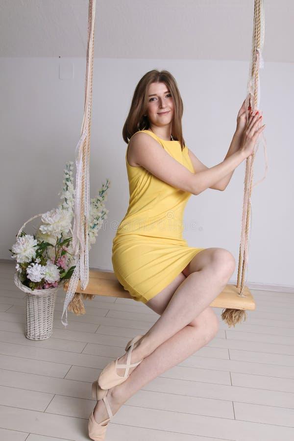 Moça no vestido amarelo no balanço na sala branca imagens de stock