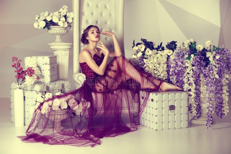 A moça no vestido com uma cor do Marsala do trem que senta-se na cadeira alta luxuosa floresce o fundo da forma fotografia de stock