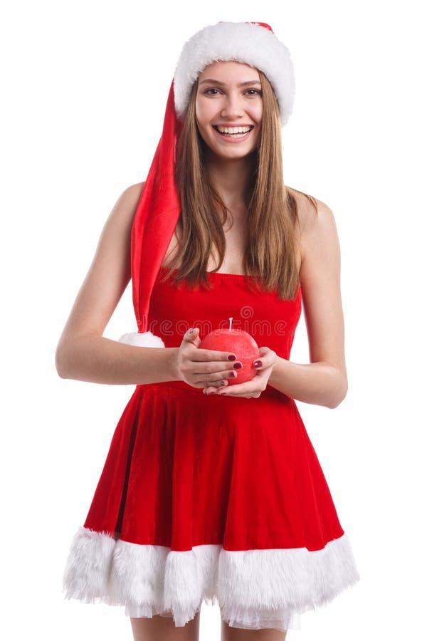Moça no vestido do Natal e no chapéu, posses um a vela vermelha redonda em suas mãos Isolado no fundo branco foto de stock royalty free