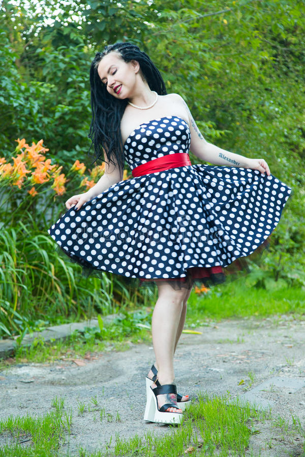 Moça no vestido do preto do vintage nas ervilhas brancas com os dreadlocks pretos no batom principal e vermelho nos bordos imagens de stock royalty free