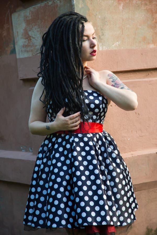 Moça no vestido do preto do vintage nas ervilhas brancas com os dreadlocks pretos no batom principal e vermelho nos bordos foto de stock