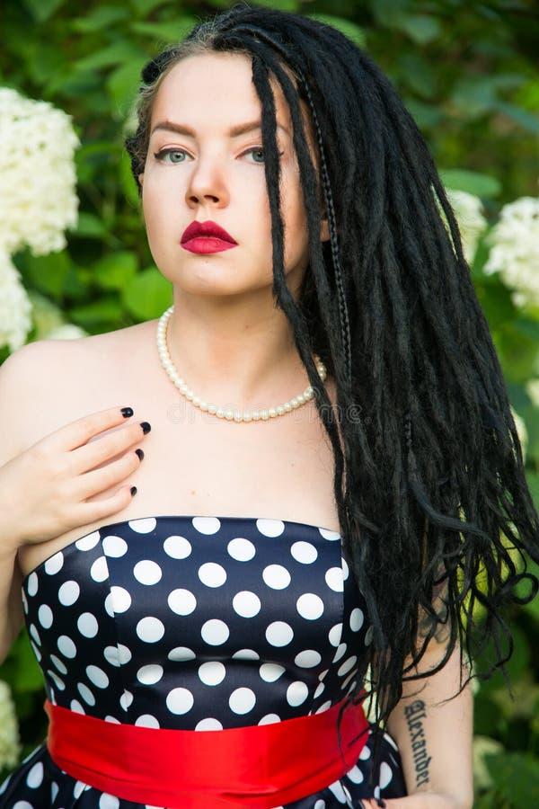 Moça no vestido do preto do vintage nas ervilhas brancas com os dreadlocks pretos no batom principal e vermelho nos bordos fotos de stock