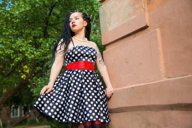 Moça no vestido do preto do vintage nas ervilhas brancas com os dreadlocks pretos no batom principal e vermelho nos bordos imagem de stock royalty free