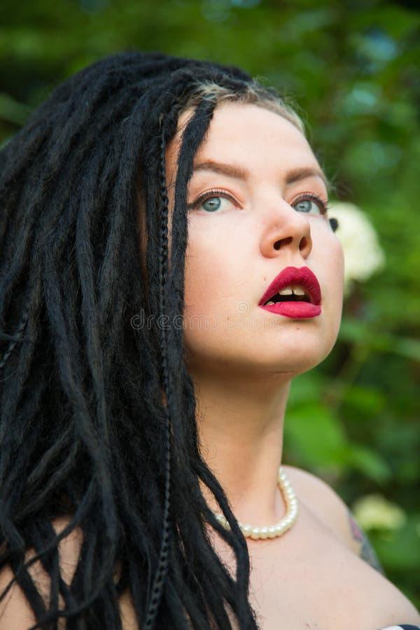 Moça no vestido do preto do vintage nas ervilhas brancas com os dreadlocks pretos no batom principal e vermelho nos bordos fotografia de stock