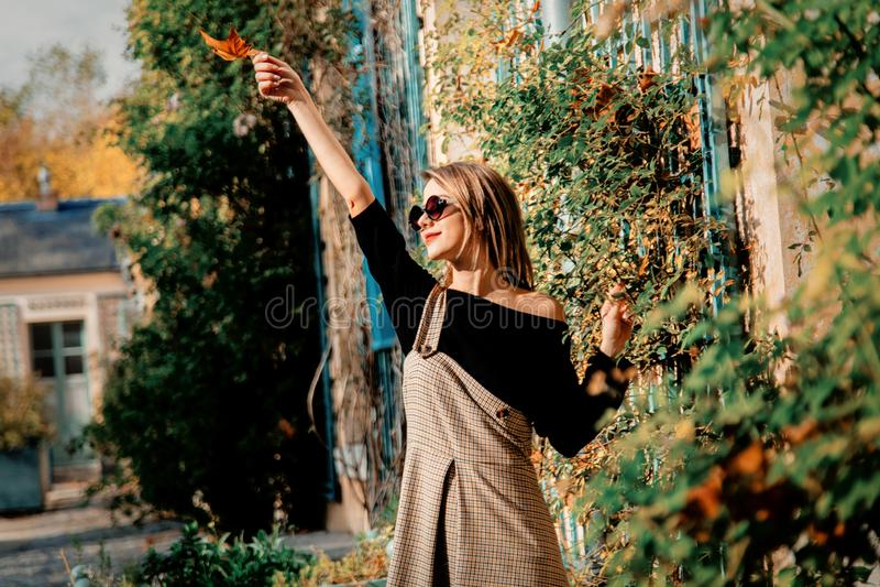 Moça no vestido e na roupa preta perto da casa fotografia de stock royalty free