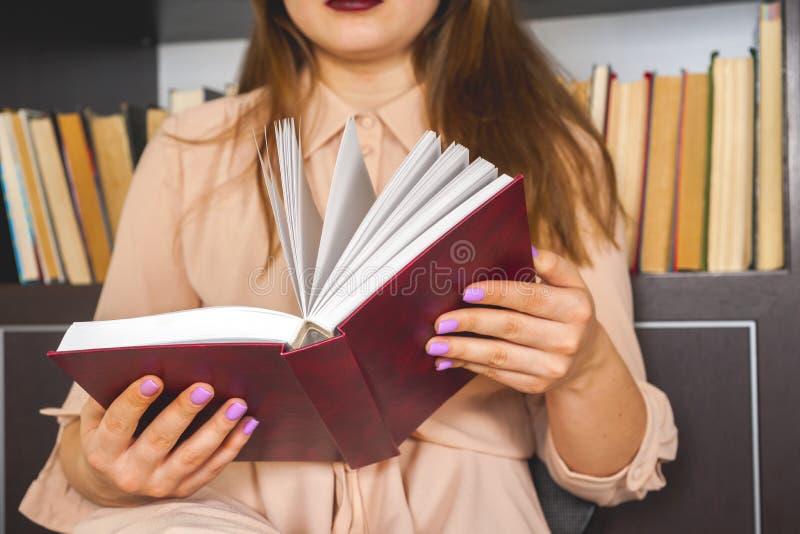 Moça no vestido luz-colorido que escolhe livros na biblioteca da universidade do vintage, livro de leitura e relaxando fotografia de stock