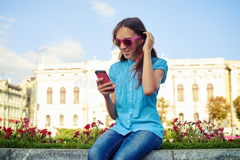 Moça nos óculos de sol que sentam-se na rua e que datilografam no sma imagens de stock
