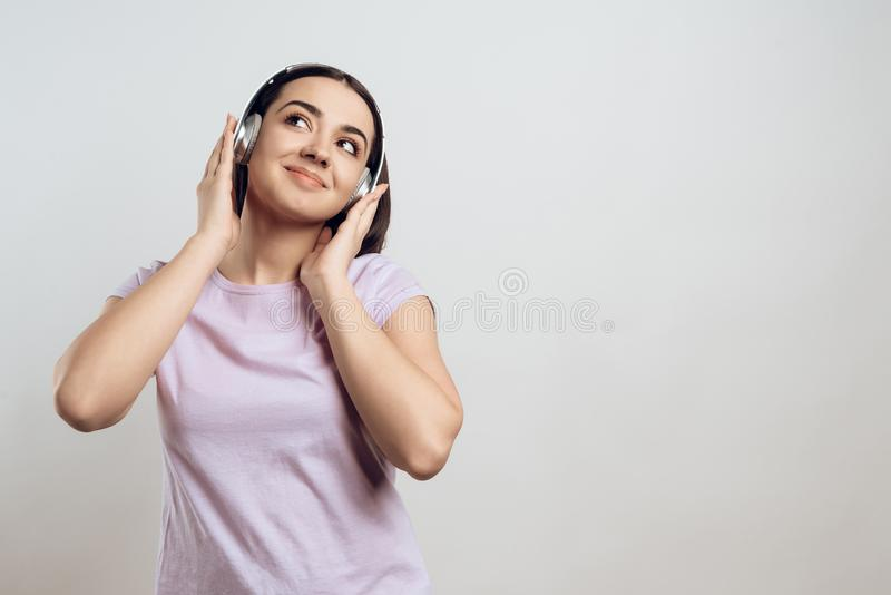 Moça nos fones de ouvido que escuta a música moderna foto de stock royalty free