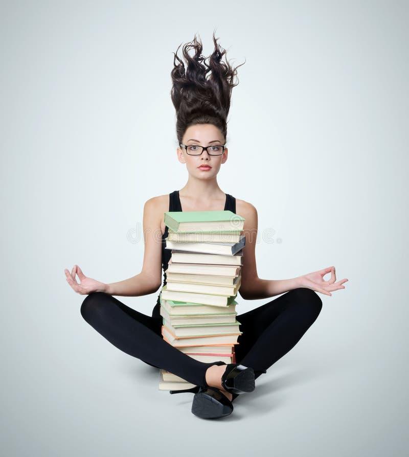 Moça nos vidros com uma pilha dos livros na posição de lótus foto de stock royalty free